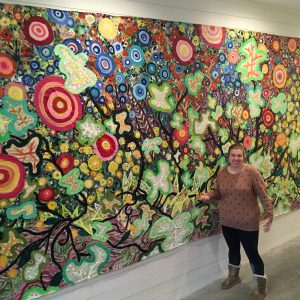 Connecticut artist Katie Jurkiewicz stands with her painting at Heirloom Flats, a luxury apartment complex in Bloomfield, CT.